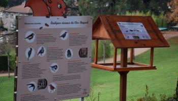 Photo de la signalétique et d'une mangeoire à oiseaux